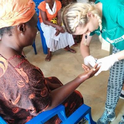 Als onderdeel van haar groepsreis Publich Health in Ghana, helpt de stagiaire een vrouw tijdens een outreach.